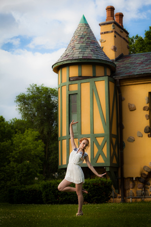 photograph of a dancing model in white dress in front of a yellow castle