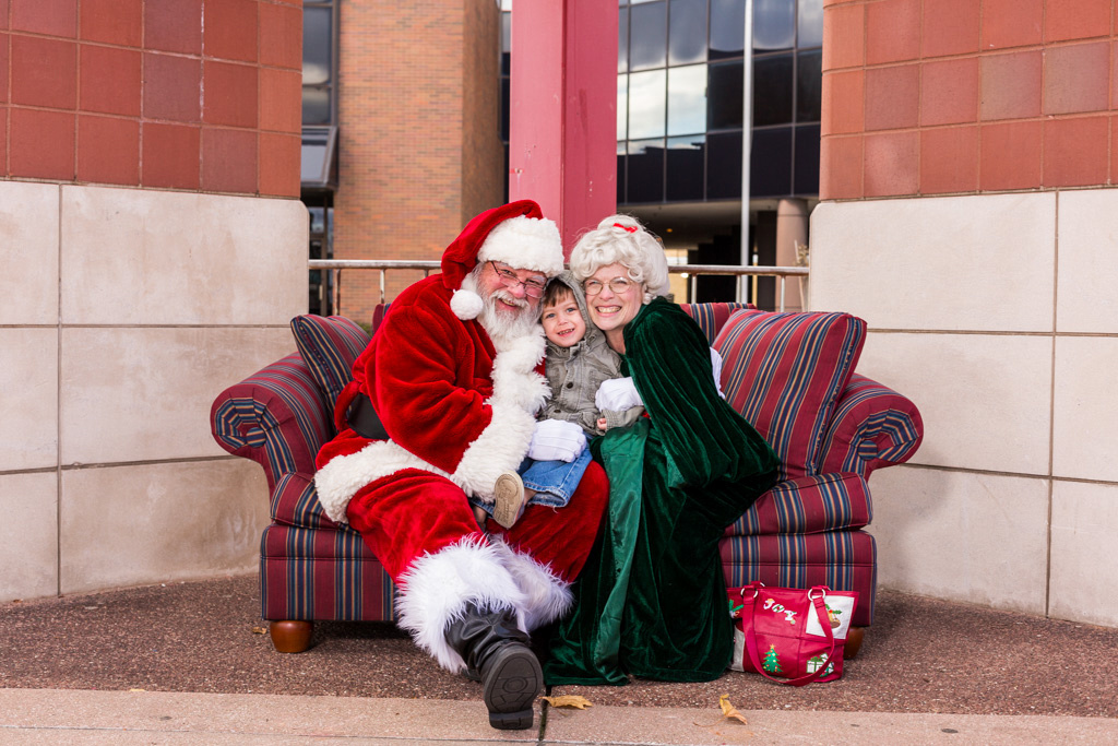 picture of a small child between Santa and Mrs. Claus