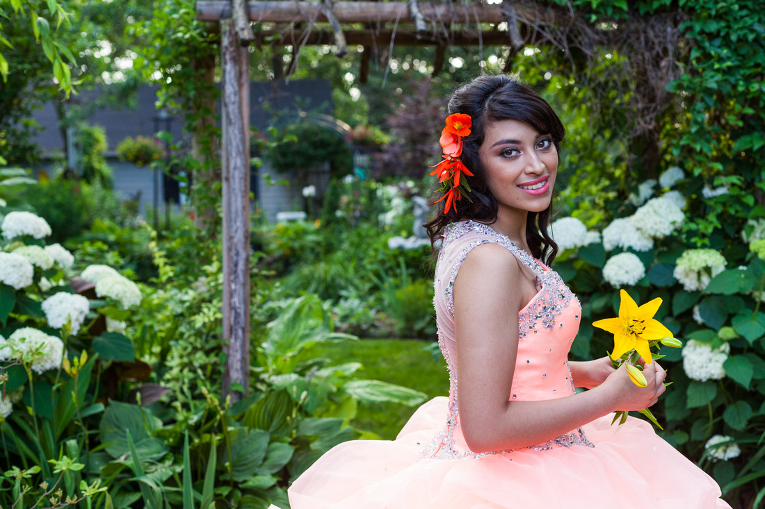 picture of young girl in Quinceañera holding aflower