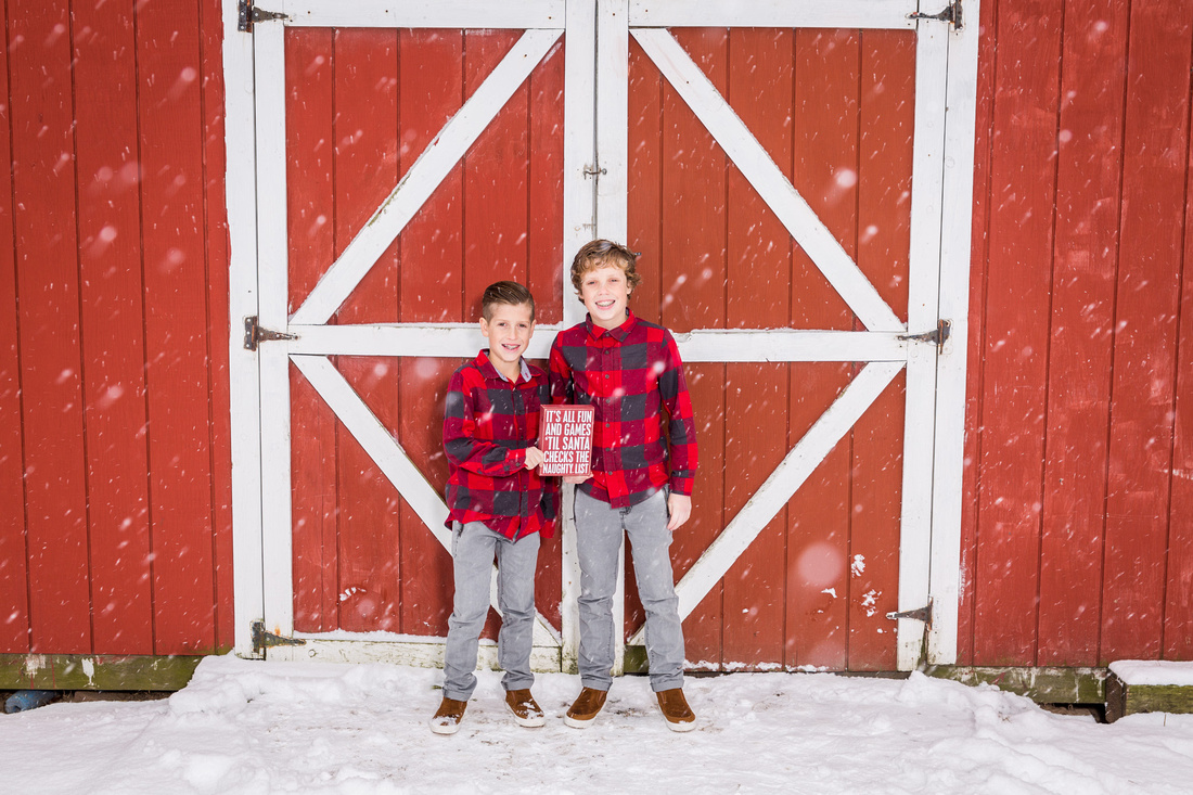 picture of  two boys in the snow in front of a red barn
