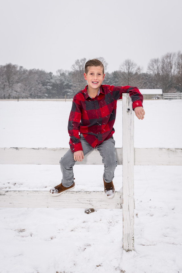 picture of boy sitting on fens in the snow.