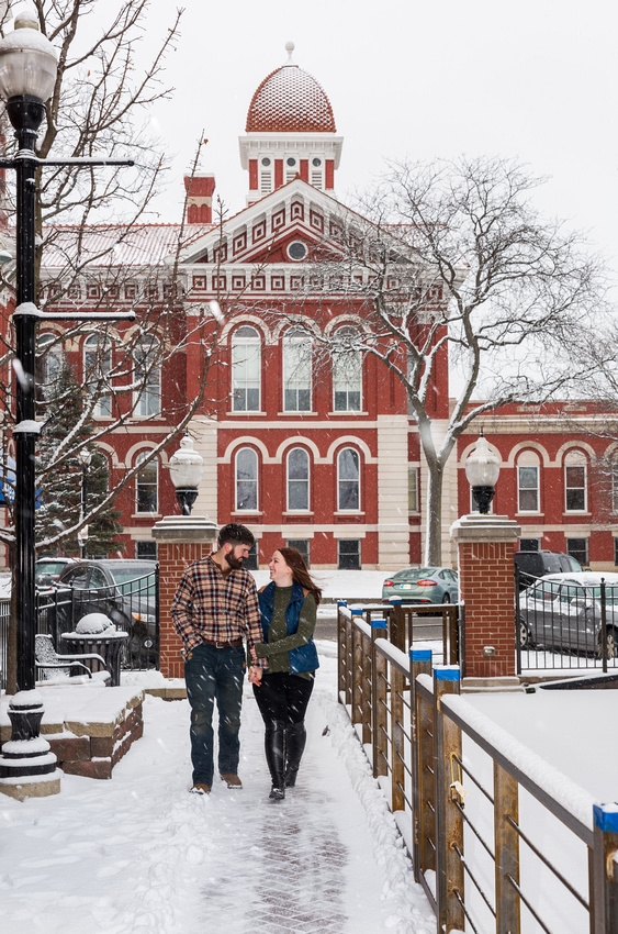 engagement picture of couple walking in front of city hall