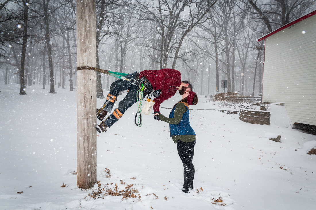 image of girl kissing telephone poll climber in the snow