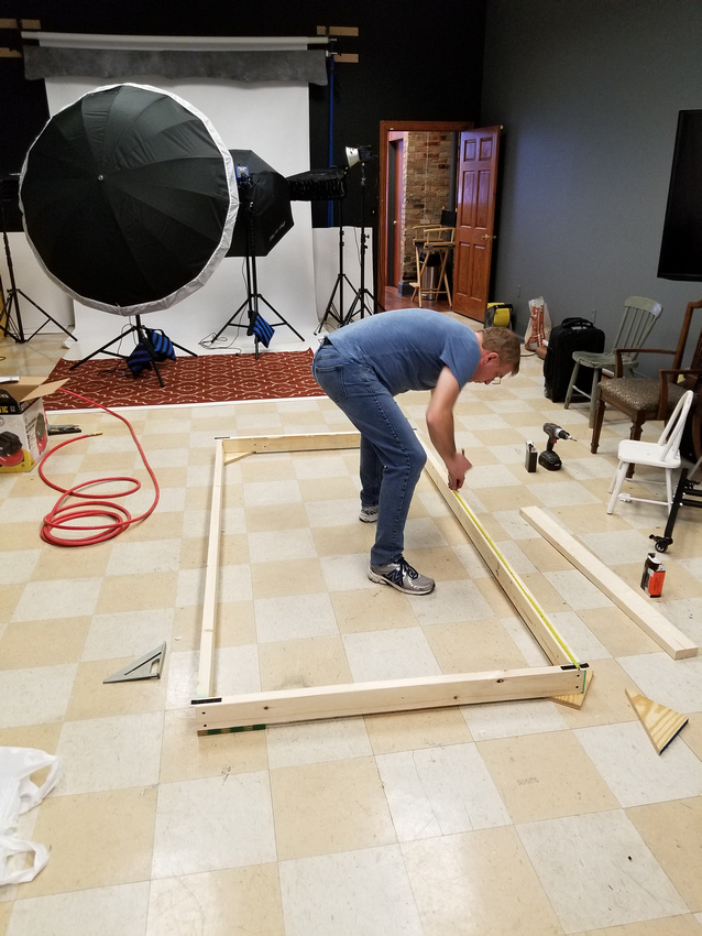 picture of man measuring lumber for photography set