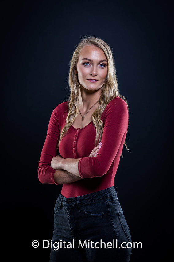 photograph of a high school senior posing in a red top and blue genes on a black background