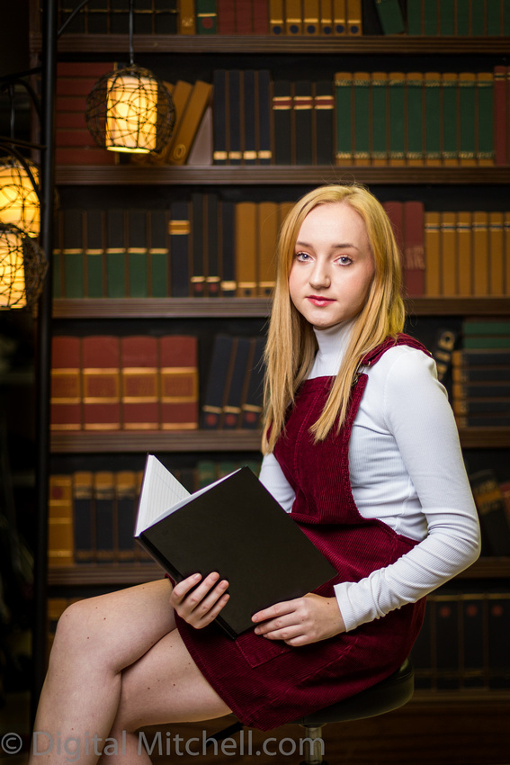 young blonde girl sitting in front of a bookshelf