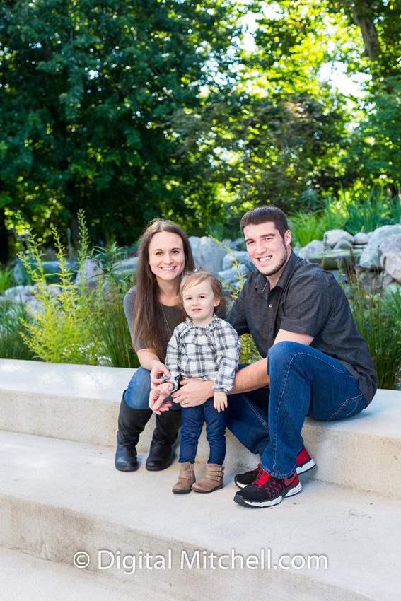 little girl with her parents for picture of family fall photo session