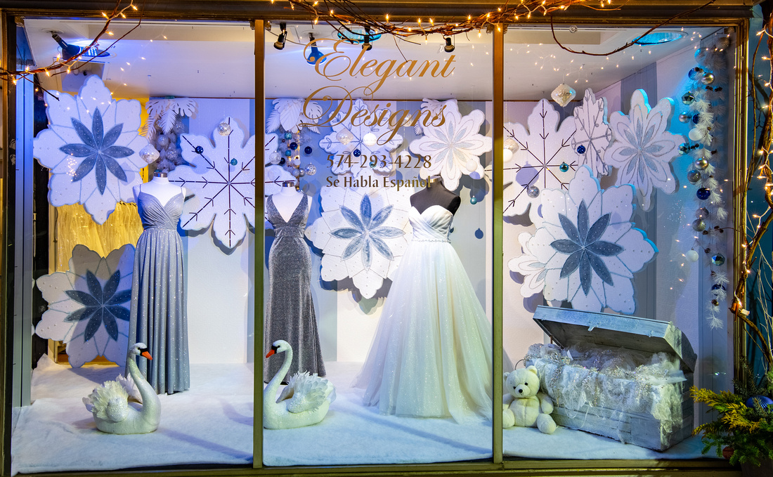 image of a store's front window with a Holiday themed dress display