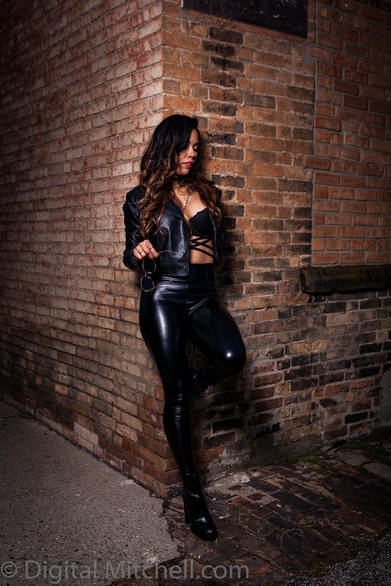 9Image of a Rocker Girl in black leather against a brick wall
