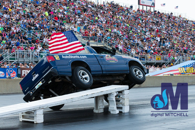 photograph of stunt truck on ramp on two wheels