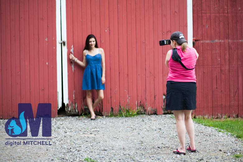Dawn photographing senior girl by barn