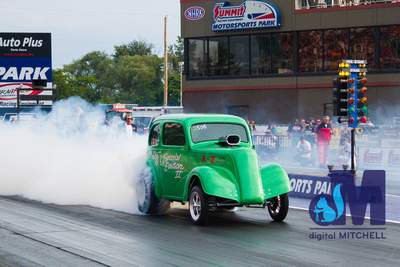 photograph of old drag racing car with smoke