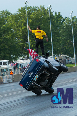 photograph of truck on two wheels and stunt man on top
