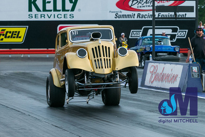 photograph of old drag racing car doing wheely