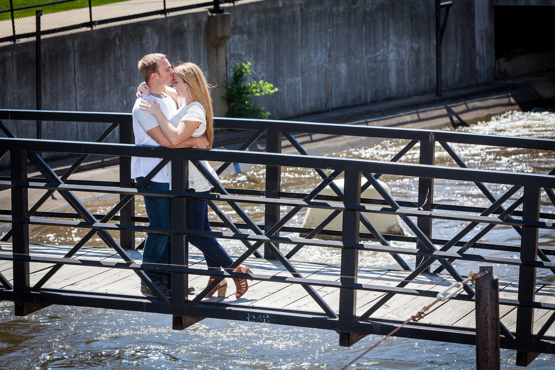 Kiss on the head while the couple stands on a bridge