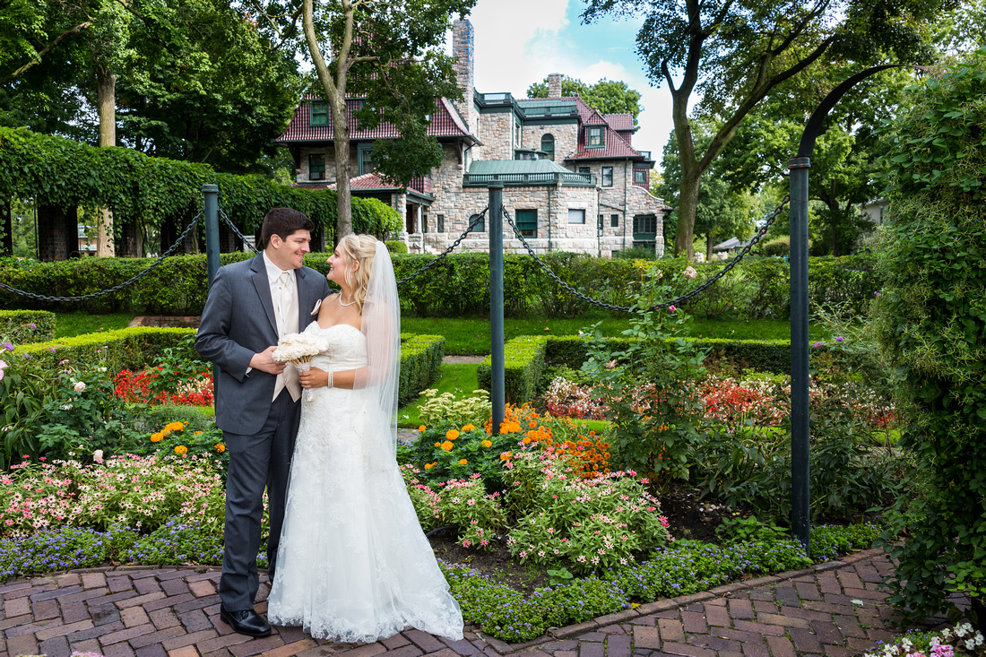 photograph of bride looking at groom by a garden