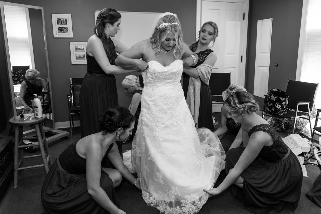 photo of bridesmaids helping the bride into her dress