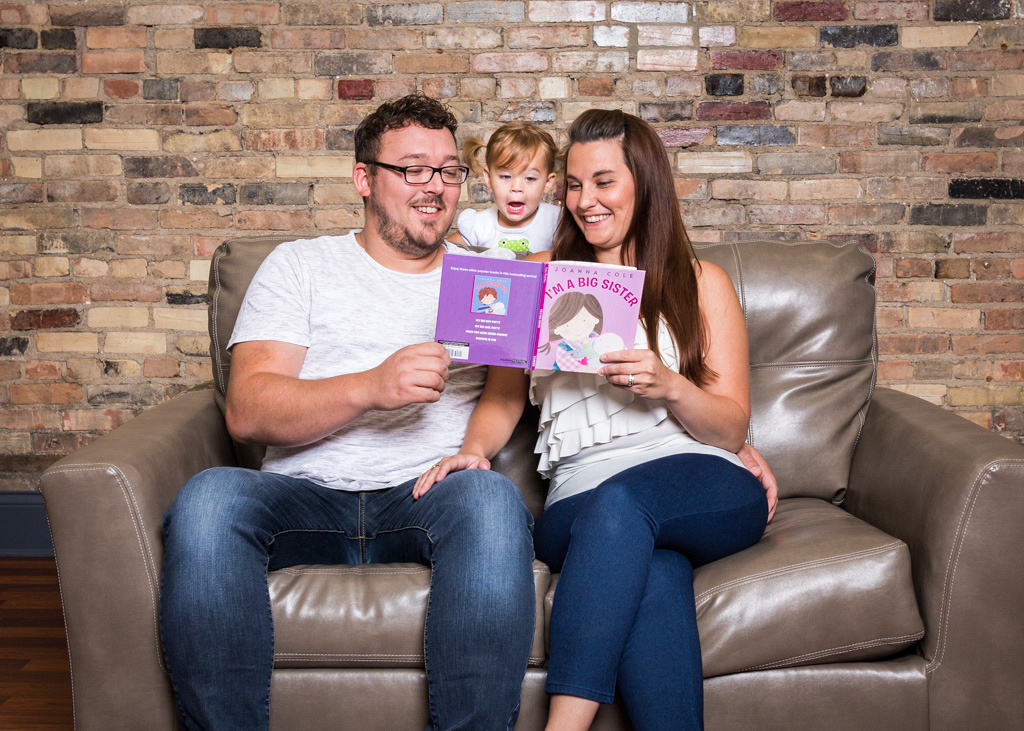 picture of mom and dad reading book to little girl