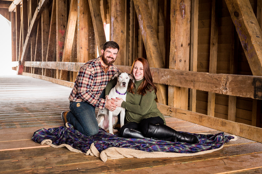 picture of couple with their dog in a covered bridge during engagement photo session