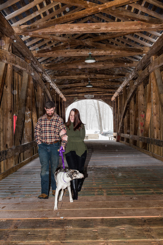 Picture of a couple walking a dog in a covered bridge