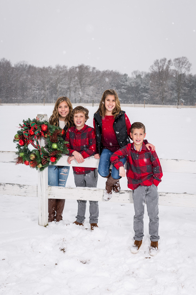 picture of kids sitting on a fens in the snow