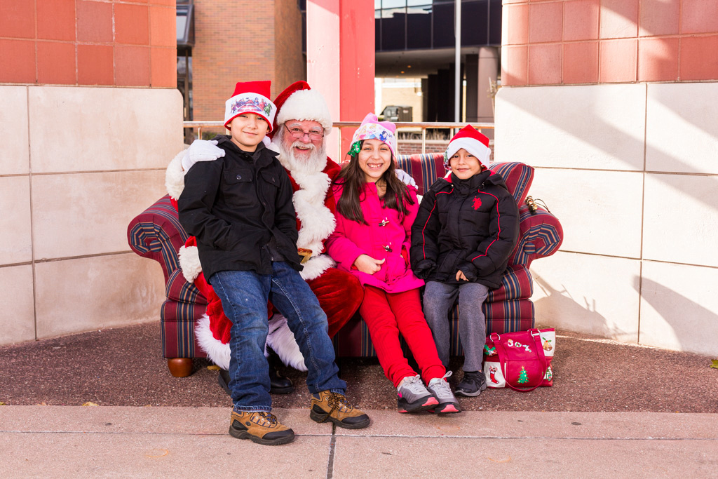 picture of Santa with kids wearing Christmas hats.