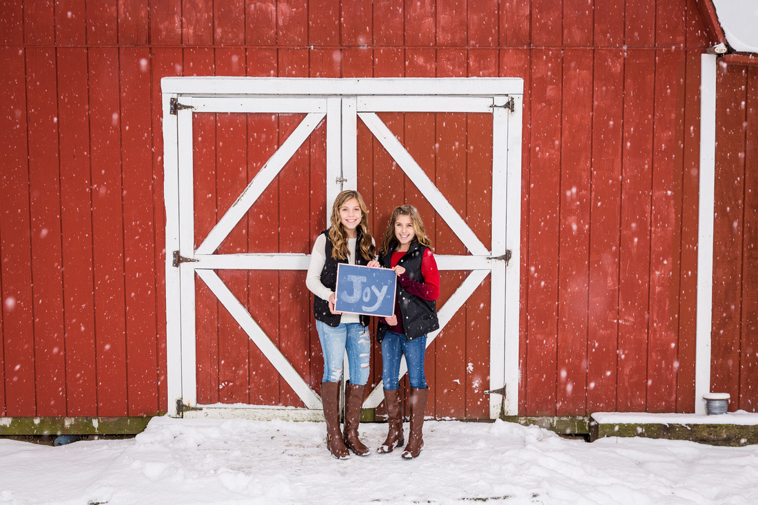 picture of two girls in the snow in front of a red barn