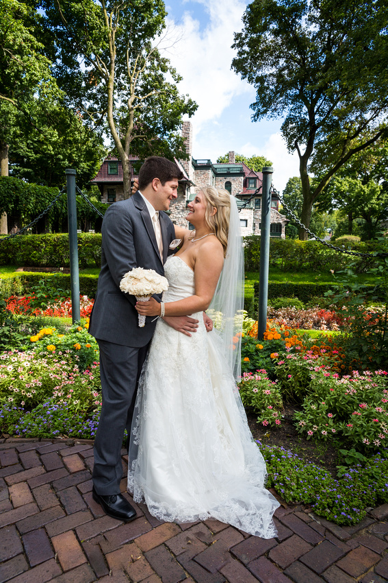 picture of an embracing bride and groom by a mansion