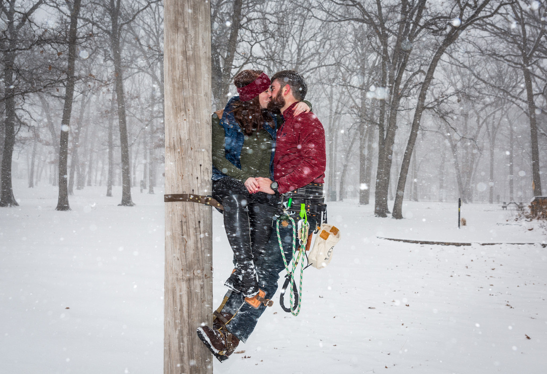 image of engagement photo session of a couple kissing while on a telephone poll